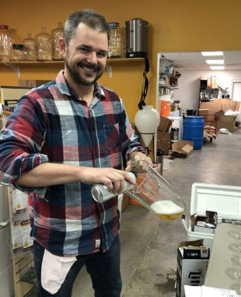 Cody McKendrick, co-owner of Salt City Brew Supply, prepares beer for a Beer Sensory Evaluation class.
