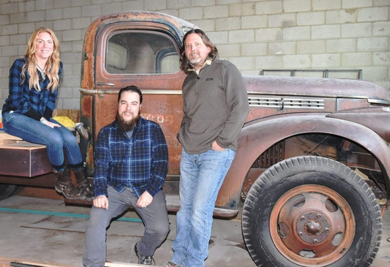 From left: Katie Flanagan, Chris Detrick, and Mark Medura sitting on a 1946 Chevy farm truck that will serve as a stage at Level Crossing Brewing.