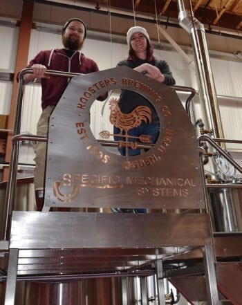 Roosters Brewery Engineer Colton Layton, left, and Head Brewer Jacquie King on the brew deck at Roosters B Street Brewery in Ogden.